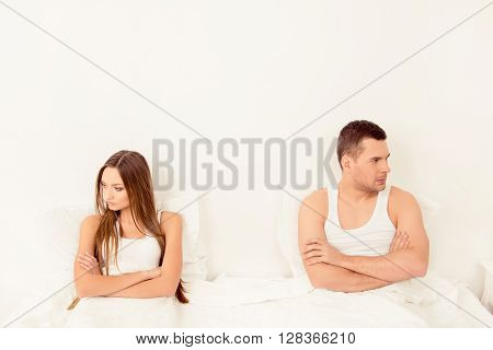 Upset Young Couple Having Marital Problems Or A Disagreement In Bed