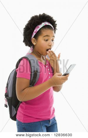 African American girl with backpack looking at cell phone with surprised expression.