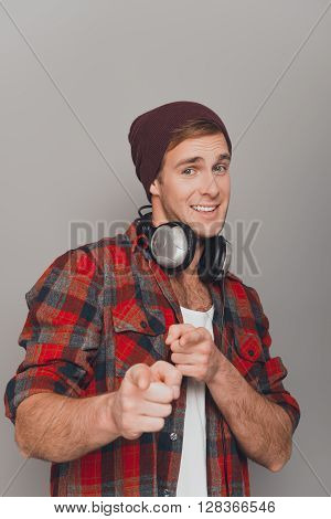 Handsome Happy Man In Cap And Earflapes Pointing On Camera