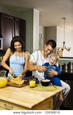 Caucasian family with toddler in kitchen at breakfast.