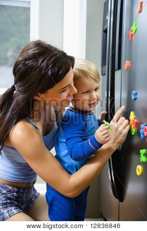 Caucasian toddler boy and mother playing with magnets on refrigerator.