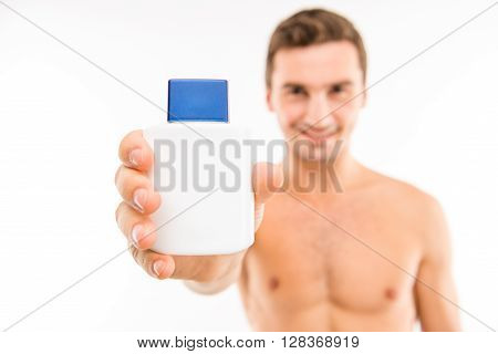 Handsome Man Showing A Lotion After Shave, Focus On Lotion