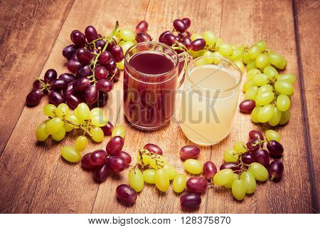 Glass of red stum and 2 glasses of white stum together with some green and red grapes photpgraphed on a piece of wood in retro style.