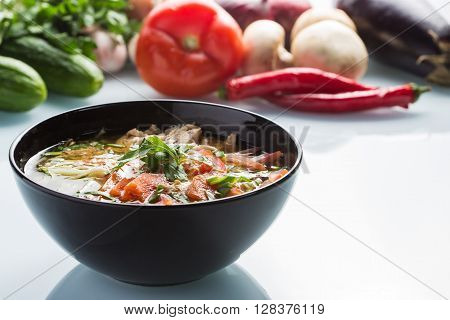 tomato soup in a black plate. red pepper fruits on the background