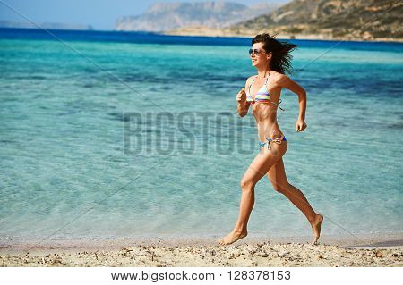 beautiful athletic woman dressed in bikini running on the beach along the sea front