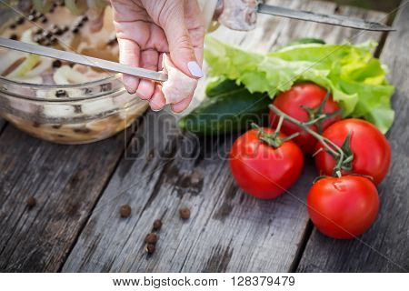 Woman Hand Sticking Meat On Skewers