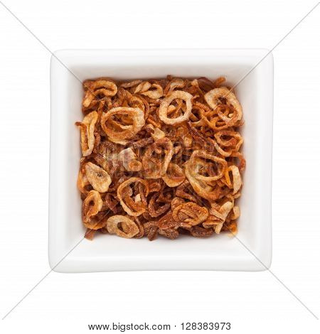 Fried sliced shallots in a square bowl isolated on white background