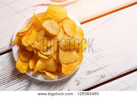 Potato chips pile on plate. Chips on white wooden background. Chips served at retro diner. Simple junk food snack.