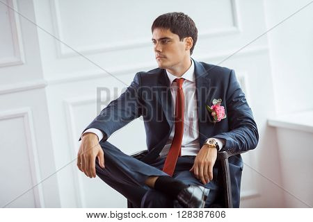 Gorgeous serious groom. Handsome man in a suite with a buttonhole sitting on chair against white wall indoors