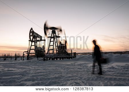 Oil worker in a oilfield. Pump jack and engineer on a winter sunset sky background. Western Siberia. Blurred motion.