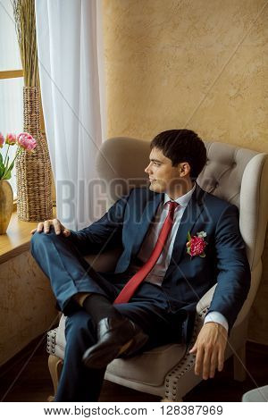 Gorgeous smiling groom. Handsome man in a suite with a buttonhole sitting on chair and looking in window indoors