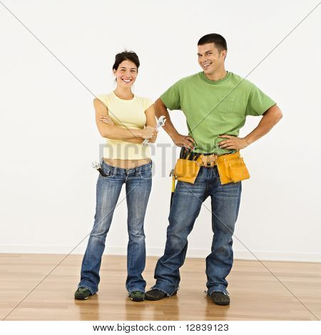 Couple with tools standing and smiling in home.