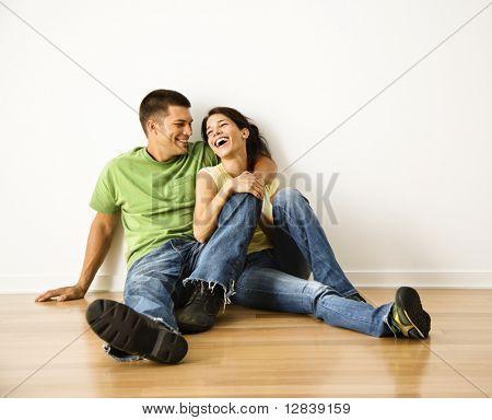 Atraente jovem casal adulto sentado perto em piso de madeira em casa sorrindo e rindo.