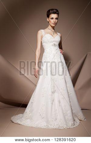 The beautiful young woman posing in a wedding dress