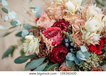 Beautiful wedding colorful bouquet for bride against nature background close-up macro shot. Beauty of colored flowers. Bridal accessories. Female decoration for girl. Details for marriage and for married couple