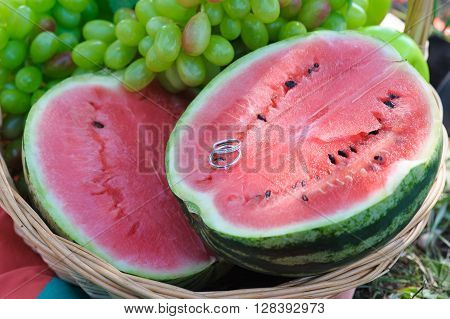 Two wedding rings on half a watermelon. Beautiful juicy watermelon. Halves fresh watermelon, grapes, appel in a basket. Wedding day.