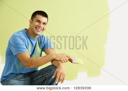 Smiling man kneeling in front of partially painted wall holding paintbrush.
