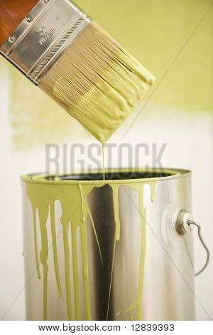 Close up of paintbrush dripping over paint can.
