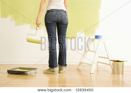 Back view of Caucasian woman holding paint roller with painting supplies.