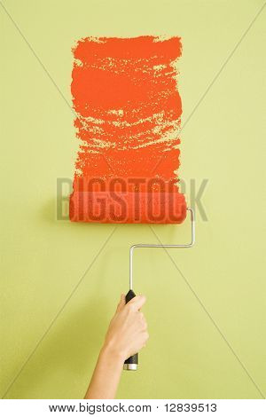 Caucasian female hand painting a green wall with a red paint roller.