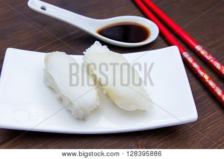 Nigiri with halibut on a wooden table seen up close
