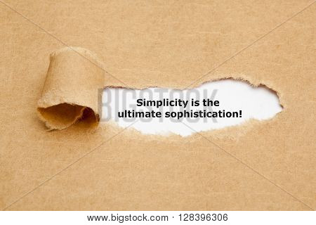 Motivational quote Simplicity is the Ultimate Sophistication appearing behind torn brown paper.