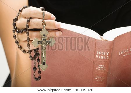 Woman holding Holy Bible open with rosary and crucifix in hand.
