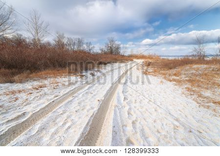 snow-covered trail / trail from the car on sandy ground