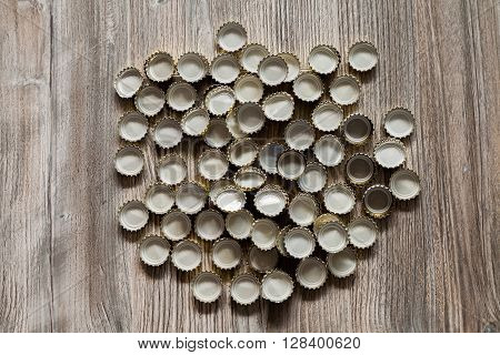 alot of bottle caps lies on wood texture