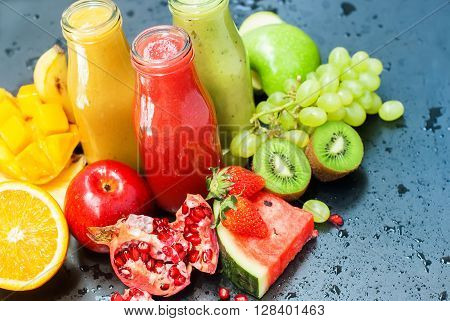 Juices Smoothie Bottles Red Green Orange Water Melon Strawberry Apple Kiwi Grapes Orange Mango Pomegranate Selective focus Black Background Healthy Concept