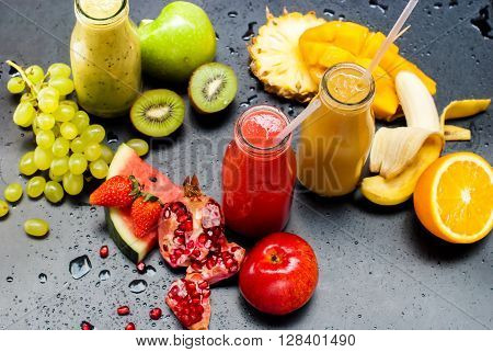 Fresh Juices Smoothie Three Bottles made Red Green Orange Fruits Water Melon Strawberry Apple Kiwi Grapes Orange Mango Pomegranate Tropical Selective focus Black Background