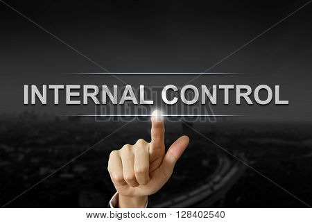 business hand clicking internal control button on black blurred background