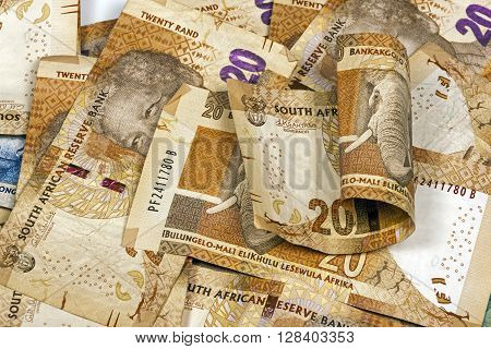 Closeup scattered collection of used South African twenty Rand brown bank notes