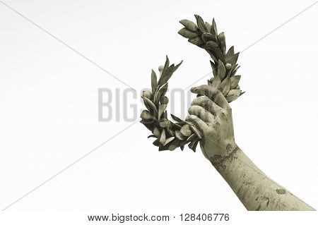 Laurel Wreath hand held by a bronze statue on white background with copy space