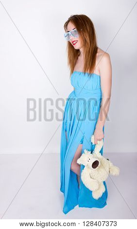 young redhead  in a blue dress and disco glasses, hugging a  in the same glasses.