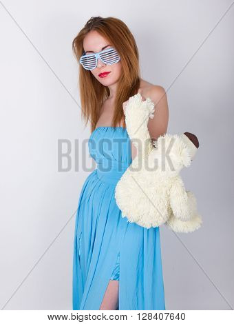 young woman in a blue dress and disco glasses, hugging a teddy bear
