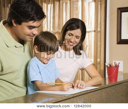 Hispanic parents helping son with homework.