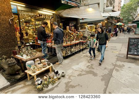 HONG KONG, CHINA - FEB 12, 2016: Antique market trader and rushing people at old city street on February 12, 2016. More than 47 million tourists visit Hong Kong annually