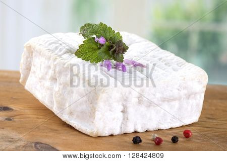 A block of Pont-l'eveque French Normandy cheese resting on wooden bord