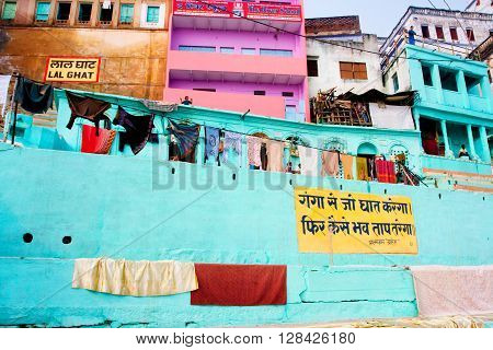 VARANASI, INDIA - JANUARY 1, 2013: Colorful Ganges River waterfront dwellings with washed clothes drying on January 1, 2013. Varanasi urban agglomeration had a population of 1435113.