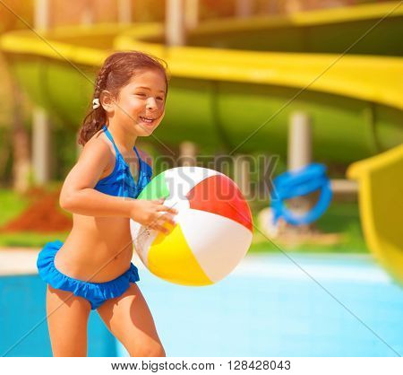 Active little girl playing with ball near pool, having fun in aquapark, water amusement, enjoying summer holidays, happiness concept
