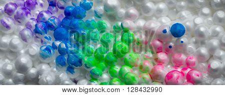 painted styrofoam balls stuck on wall close-up.