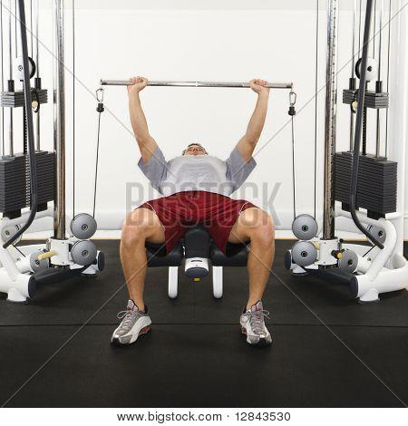 Muž v tělocvičně zvedání závaží o hmotnosti stroje.