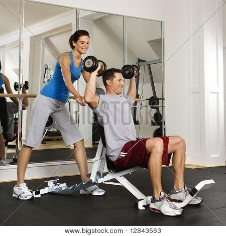 Woman spotting man lifting weights at gym.