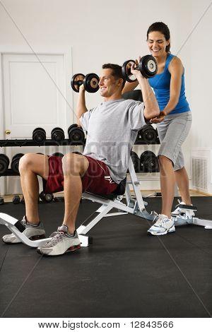 Mujer ayudando a levantar pesas en el gimnasio del hombre.