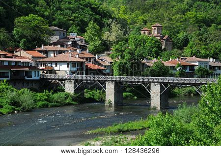 VELIKO TARNOVO, BULGARIA - MAY 1, 2016: Wooden bridge in Asenov district of the town and St. Dimitri Church in the background