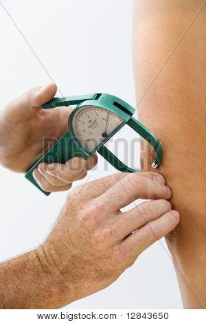 Close-up of adult male hand using caliper to test body fat.