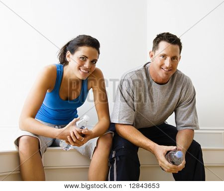Portrait of young adult woman and man sitting wearing active wear.