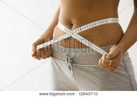 Woman standing pulling measuring tape around waist.