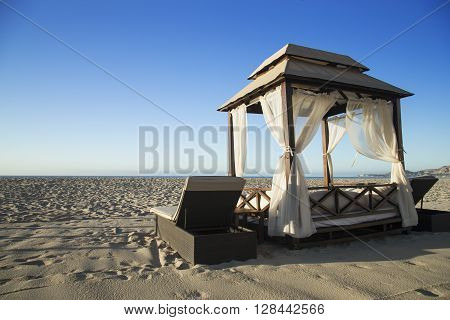 a single beach cabana waits on the tropical beach ready for the day
